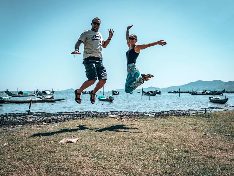 Lee and James jumping in front of lagoon on Hue to Hoi An bike ride