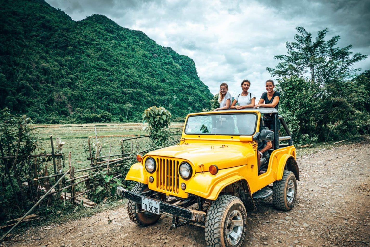 Picture of girls in yellow jeep going to Vang Vieng viewpointLaos
