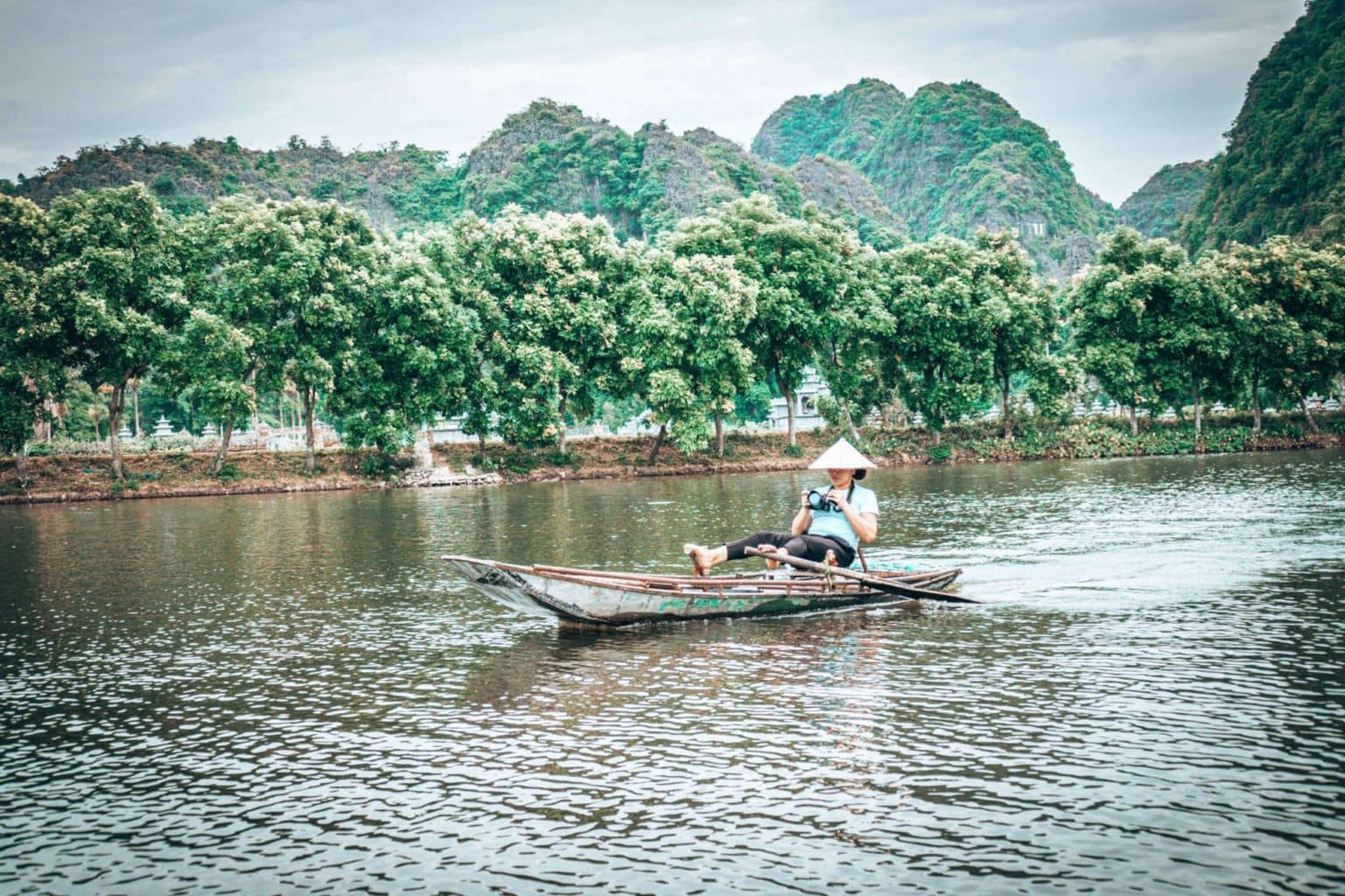 Woman rowing boat with her feet in Tam Coc Vietnam